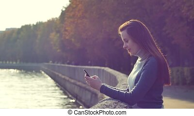 Young woman with red hair writing sms in the autumn park near the water