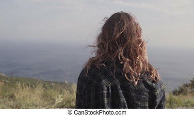 Woman with pink hair standing on the mountain top over blue...