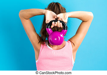 Happy woman working out with kettlebell