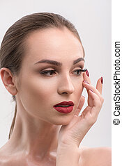 Young woman with red lips and nails in studio - Ravenous...