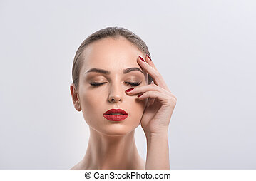 Young woman with red lips and nails in studio - She is...