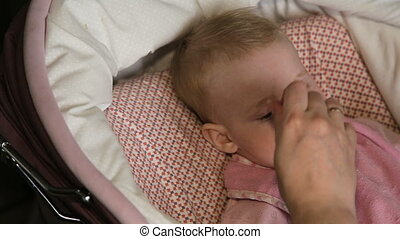 Mother feeding her baby by spoon. - Mother feeds her baby...