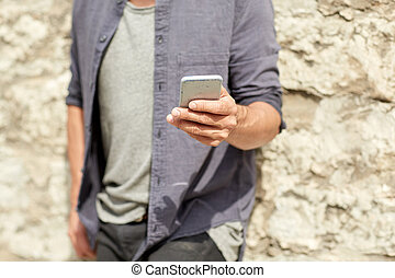 close up of man with smartphone at stone wall