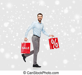 smiling man with red shopping bags over snow - people, sale,...