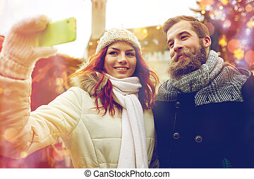 couple taking selfie with smartphone in old town - holidays,...