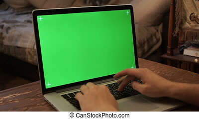 Male hands typing on a green screen laptop.