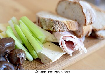 Artisan bread board with cheese, ham, celery and balsamic...