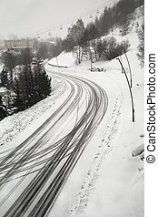 Snowy road in the mountains - Road in falling snow in the...