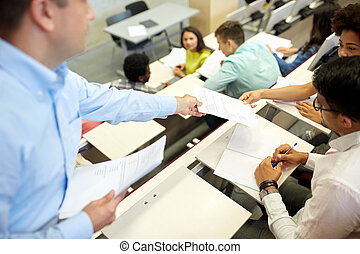 teacher giving tests to students at lecture hall -...