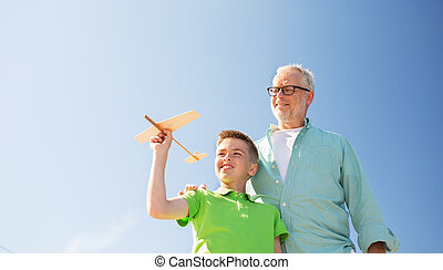 senior man and boy with toy airplane over sky - family,...
