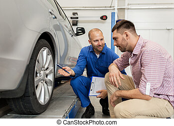 auto mechanic with clipboard and man at car shop - auto...