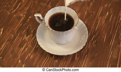 Pouring milk into a cup of coffee.