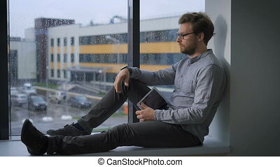 Pensive young man sitting at window. Rainy day. Cityscape at...