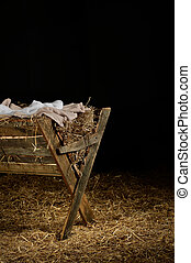 Manger with Clothes on Hay - View of manger on straw covered...