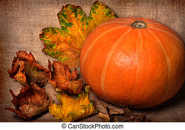 Fall background - Pumpkin and fall leaves on sacking...