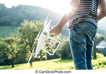 Unrecognizable young man holding drone. Sunny green nature....