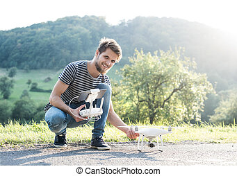Young hipster man holding drone. Sunny green nature. - Young...