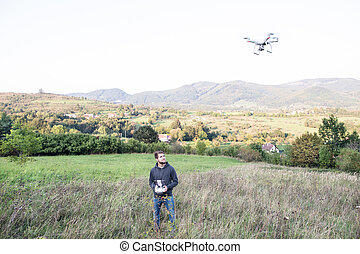 Young hipster man with flying drone. Sunny green nature. -...