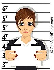Arrested businesswoman posing for mugshot holding a...