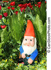 Garden gnome sitting among fern and tulips
