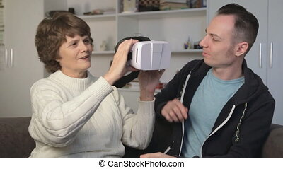 Young man showing virtual reality glasses to an old woman....