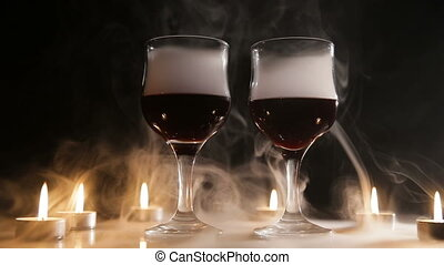 Wine glasses and burning candles in the smoke. - Two glasses...