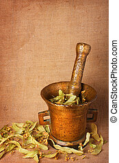 Old bronze mortar with herbs - Old bronze mortar with dry...
