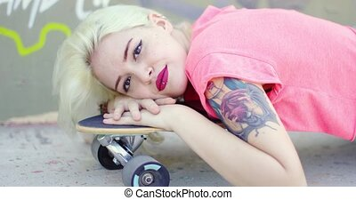 Pretty young blond woman with an arm tattoo lying resting...