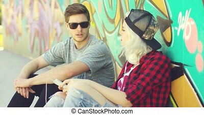 Hipster couple relaxing against a graffiti wall - Young...
