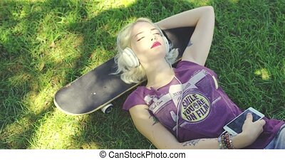 Young blond woman relaxing listening to music - Pretty young...