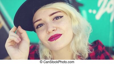 Gorgeous young blond woman with a pierced lip wearing a...