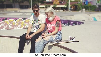 Young couple of skateboarders sitting chatting at the skate...