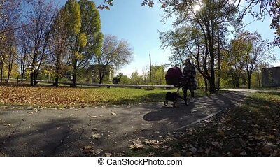 Young stylish mother walking with her baby in city in autumn...