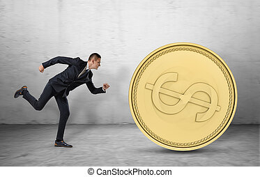 Young businessman running to catch a big golden coin