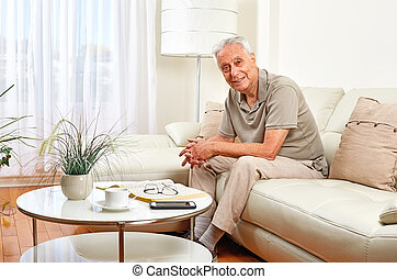 Senior man at home. - Elderly retired man sitting sofa in...