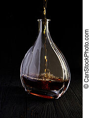 Glass decanter with brandy on black background