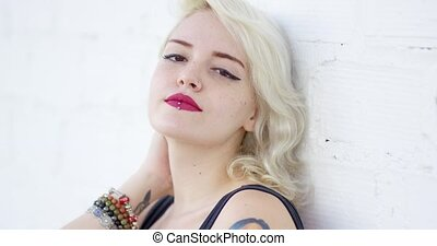 Portrait of a sexy hipster young blond woman with a lip...