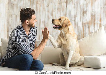 happy guy sitting on a sofa and looking at dog - high five...