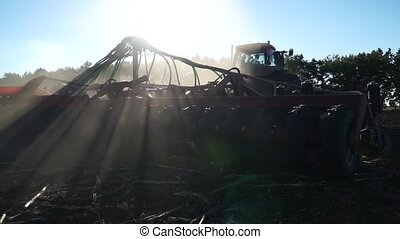 Seed drill in a dusty field - The sun breaks through the...