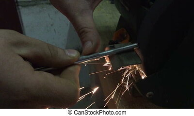 Grinding of metal parts using a grinder with sparks