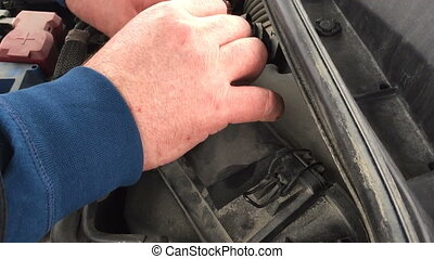 man closes the air filter under the hood of a car. Car...