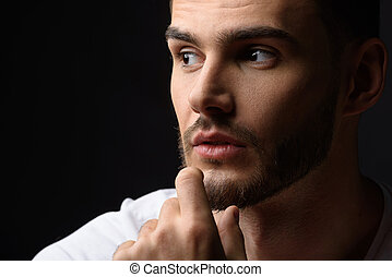 face of a calm man in studio - thoughtful bearded guy with...