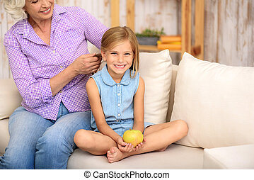 Mature woman weaving braid for her grandchild - Kind...