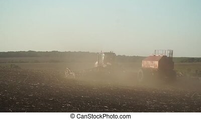 Tractor working in the dust - On a wide field lone tractor...