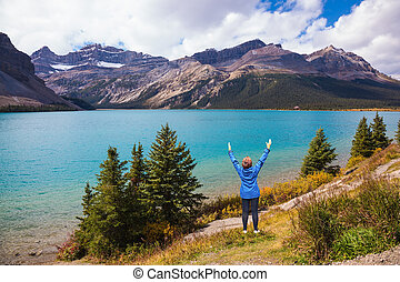 Middle-aged woman in awe threw up her hands - Bow Lake in...