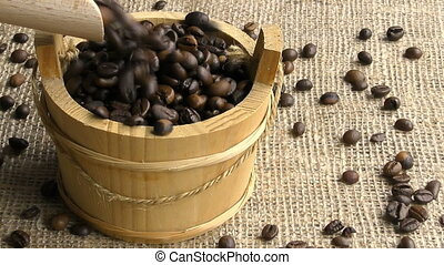 coffee beans - fill a wooden bucket of coffee beans in slow...