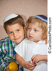 Two beautiful Jewish boy in skull-caps. The elder brother...