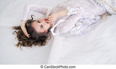 Girl in white dress lying on the studio floor and posing for...