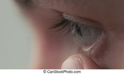 Young handsome man putting contact lens in her eye close up....