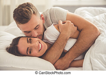 Beautiful young couple - Handsome young man is hugging and...